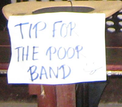 The sign reads 'TIPS FOR THE POOR BAND'...