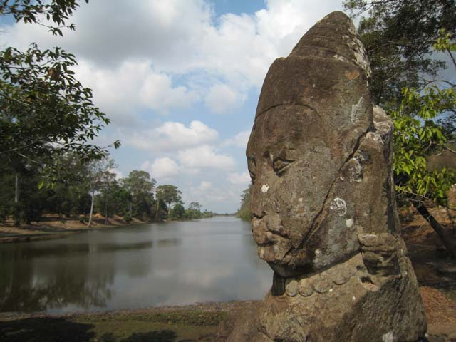 A deva head overlooking the moat round Angkor Thom